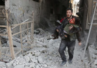 A Syrian man rescuing a child after an air strike on Eastern Ghouta, near Damascus, on February 21