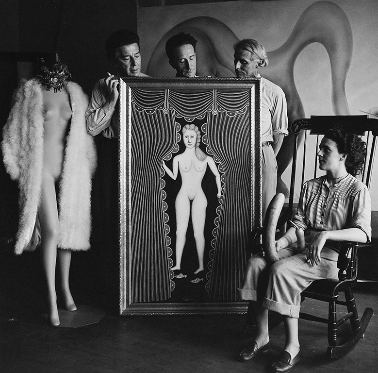 Leonora Carrington with André Breton, Marcel Duchamp, and Max Ernst, New York City, 1942; photograph by Hermann Landshoff. At center is Morris Hirshfield's painting Nude at the Window (1941).