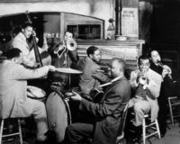 Louis Armstrong, second from right, in the 1947 film New Orleans. With him are, from left, Zutty Singleton (drums), Red Callender (bass), Kid Ory (trombone), Charlie Beal (piano), Bud Scott (guitar), and Barney Bigard (clarinet).