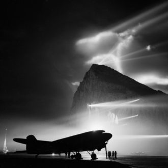 A British airplane silhouetted by searchlights on the Rock of Gibraltar as it prepared for a flight to the United Kingdom, circa 1943