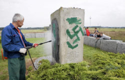 A worker cleaning a monument to the victims of the 1941 Jedwabne pogrom after it was defaced by neo-Nazis, Poland, 2011