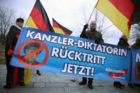 Supporters of Germany's far-right AfD party holding a banner that reads,