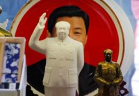 Sculptures of Chinese Chairman Mao Zedong in front of a souvenir plate with a portrait of Chinese President Xi Jinping, Tiananmen Square, Beijing, March 1, 2018