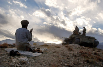 An Afghan soldier praying near Tora Bora during fighting against the Taliban, December 2001