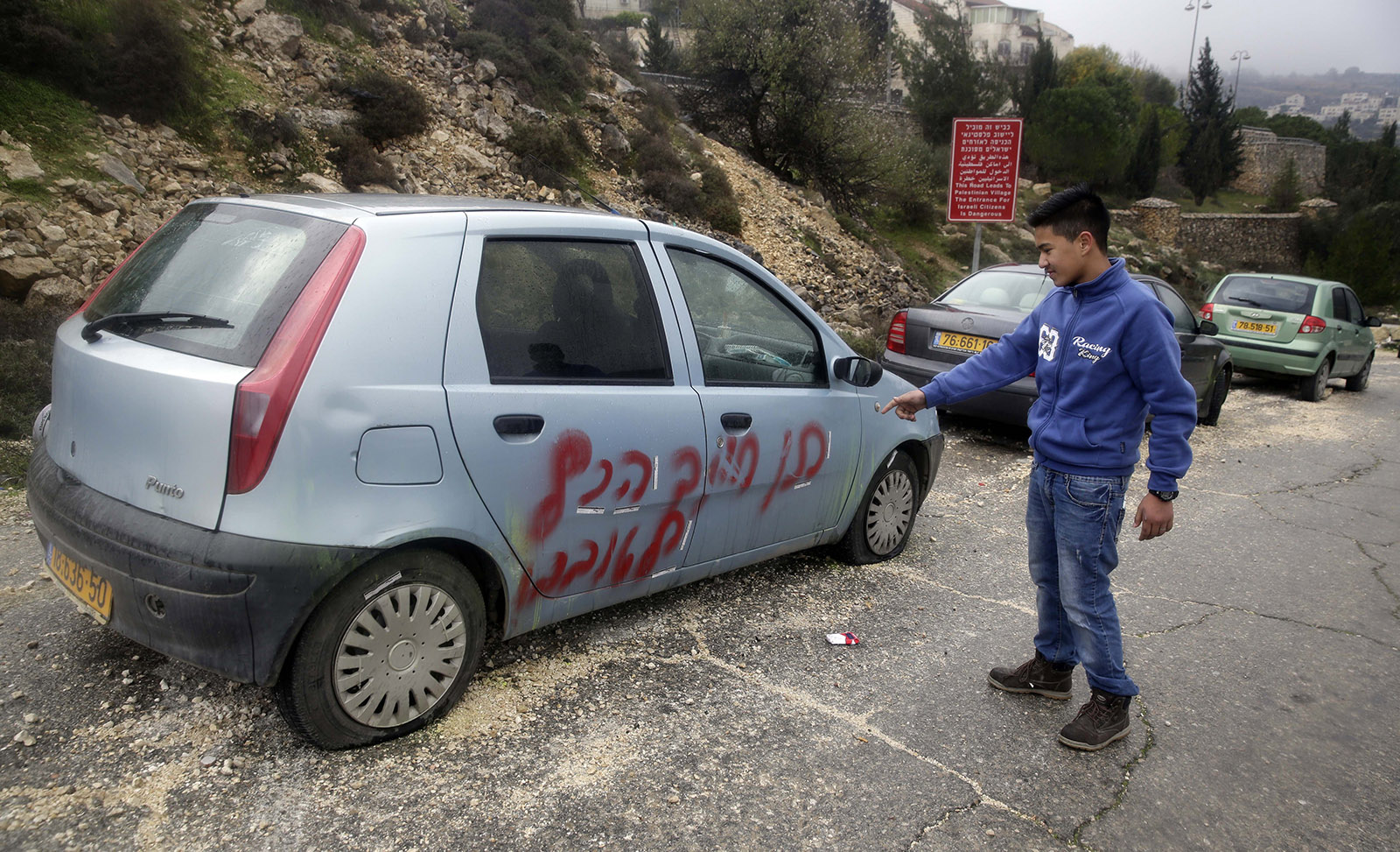 A Palestinian boy pointing to a car vandalized and daubed with racist slogans by Israeli settlers in Beit Iksa, a West Bank village near Jerusalem, January 17, 2018