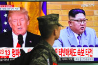 A South Korean soldier passing giant TV screen images of US President Donald Trump and North Korean leader Kim Jong-un in Seoul, South Korea, on March 9, 2018