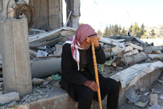A Syrian man resting amid the rubble of a home in Afrin, March 31, 2018