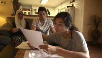 A still showing Assia Boundaoui sharing FBI documents with her family, from Boundaoui's The Feeling of Being Watched, 2018