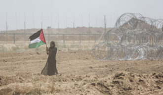 A Palestinian woman on the Gaza side of the fence on a day of bloody protests at the buffer zone with Israel, May 14, 2018