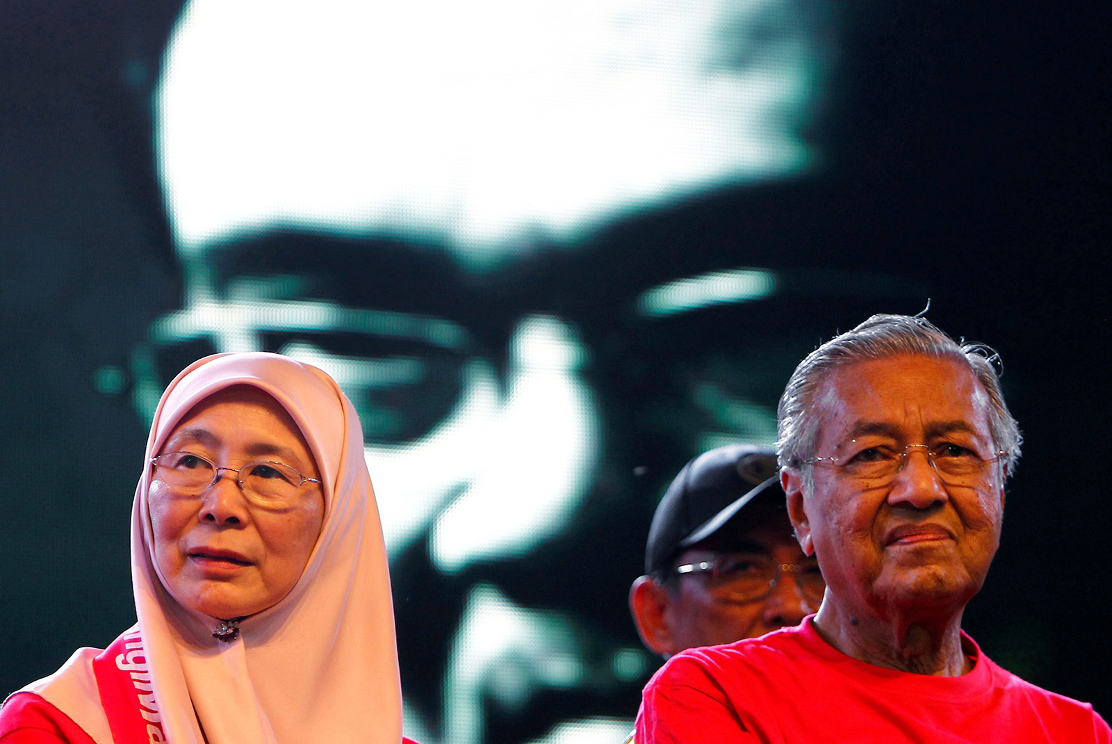 A video clip of the then jailed opposition leader Anwar Ibrahim playing in the background at an anticorruption rally with Anwar's wife, Wan Azizah, and Anwar's one-time nemesis but now political ally, Malaysia's former prime minister, Dr. Mahathir Mohamad, in Petaling Jaya, Malaysia, October 14, 2017