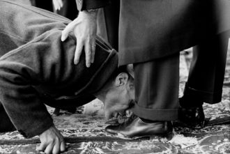 A peasant kissing the feet of Mohammad Reza Shah Pahlavi during a ceremony to distribute land deeds, Isfahan, 1962