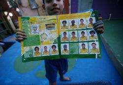 A boy from Santa Marta favela with his Panini World Cup sticker book, Rio de Janeiro, Brazil, 2014
