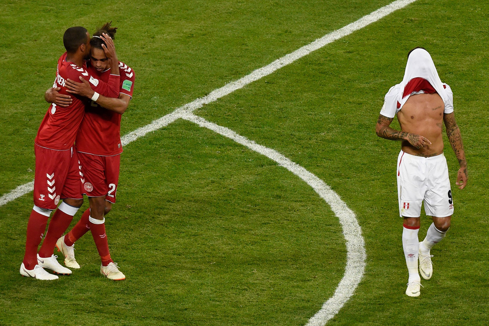 Danish players congratulating each other and Peru's star forward Paolo Guerrero covering his face with his shirt as Peru lost 0-1 to Denmark in Saransk, Russia, June 16, 2018