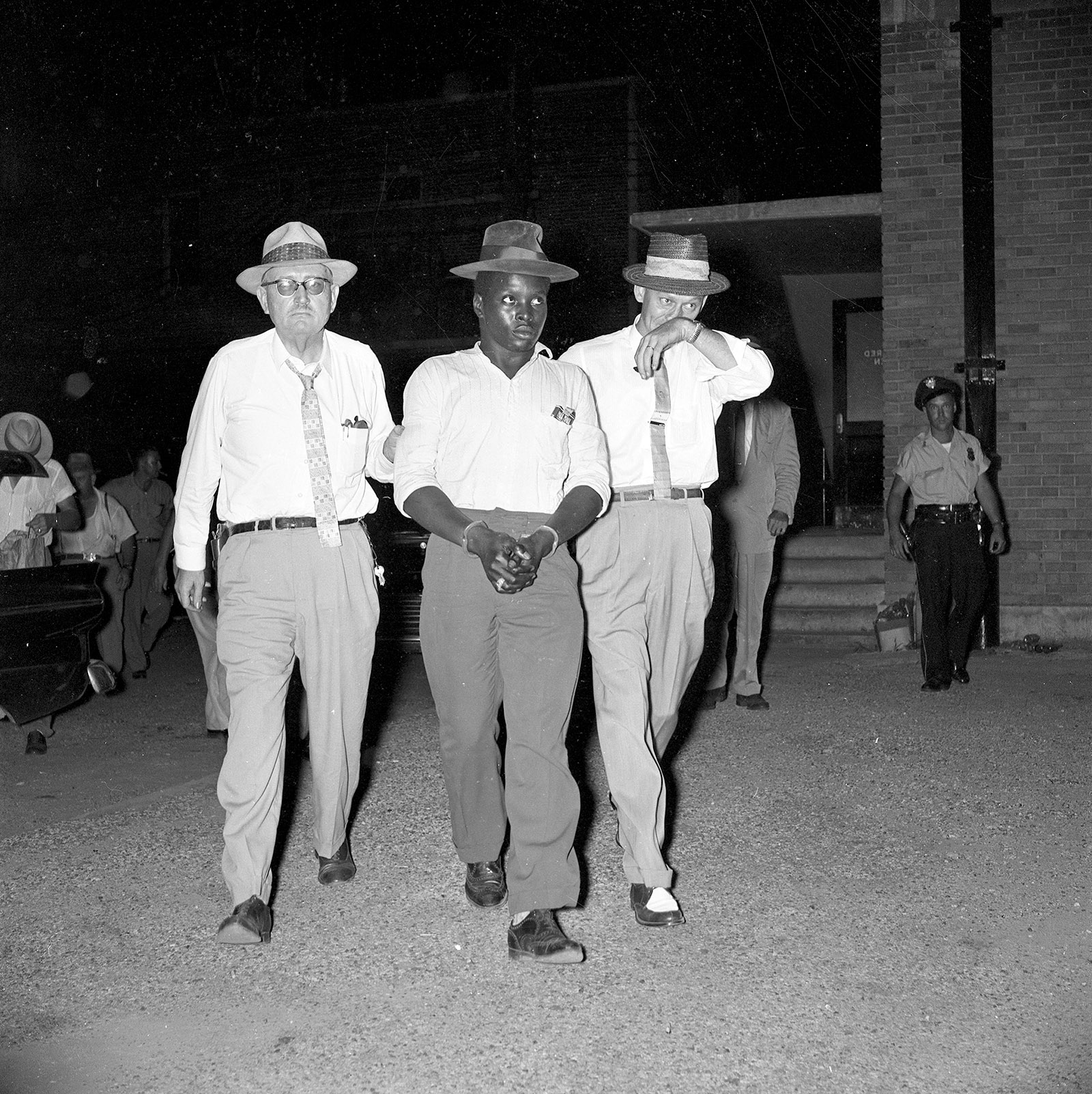 Caliph Washington arriving at the Jefferson County Jail in Bessemer, Alabama, escorted by Deputy Sheriff Clyde Morris and Police Chief George Barron, 1957