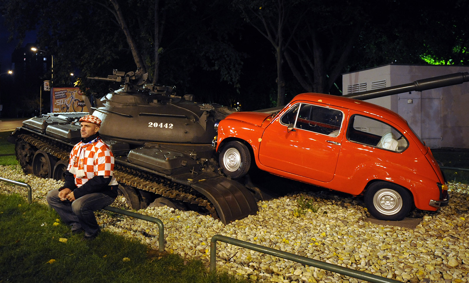 A Croatian football fan sitting in front of an art installation showing a former Yugoslav National Army tank in collision with a small red car, commemorating an actual event regarded by many as marking the beginning of the 1991–1995 war, Osijek, eastern Croatia, 2012