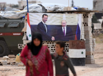 A Syrian woman and boy walking past a Syrian government checkpoint in western Idlib province, June 1, 2018