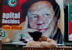A man on his cell phone sitting in front of a poster showing Imran Khan, head of the Pakistan Tehreek-e-Insaf party, which won this past week's elections, Islamabad, Pakistan, July 28, 2018