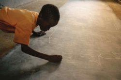 A boy writing on a blackboard in Lokichogio, Kenya, 2002