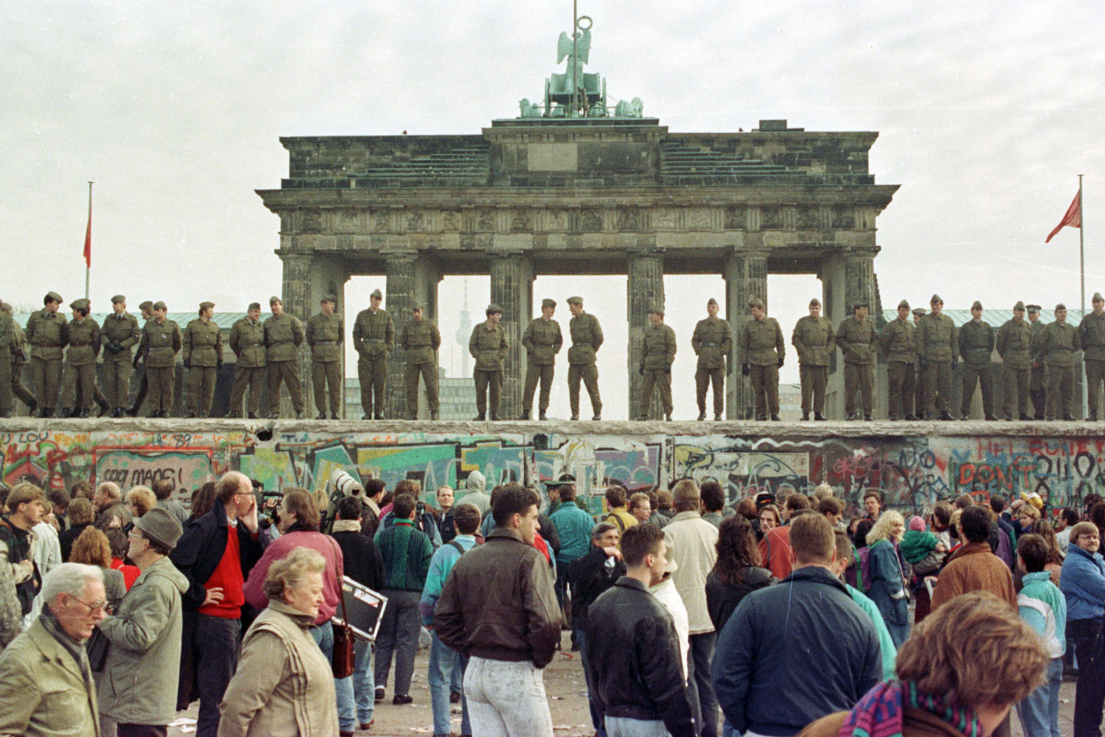 East Berlin border guards standing atop the Berlin Wall in front of the Brandenburg Gate, November 11, 1989