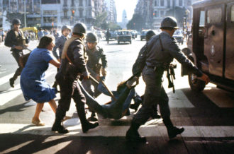 A woman trying to prevent the detention of a young man arrested by police at a protest rally against Argentina's military dictatorship, Buenos Aires, March 30, 1982