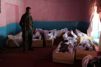 An Afghan policeman next to the coffins containing corpses following clashes with Taliban fighters, Ghazni, August 14, 2018