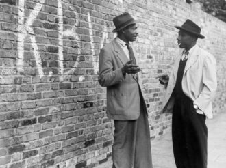 """Two men talking in a Brixton street; in the background, the graffiti stands for """"Keep Britain White,"""" London, June 9, 1952"""