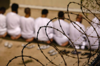 A group of detainees kneeling in prayer in the US prison camp at Guantánamo Bay, Cuba, October 28, 2009