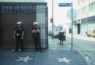 Two LAPD officers the morning after rioting reached Hollywood Boulevard following the acquittals of some of the LAPD officers who violently beat Rodney King the year before, Los Angeles, 1992