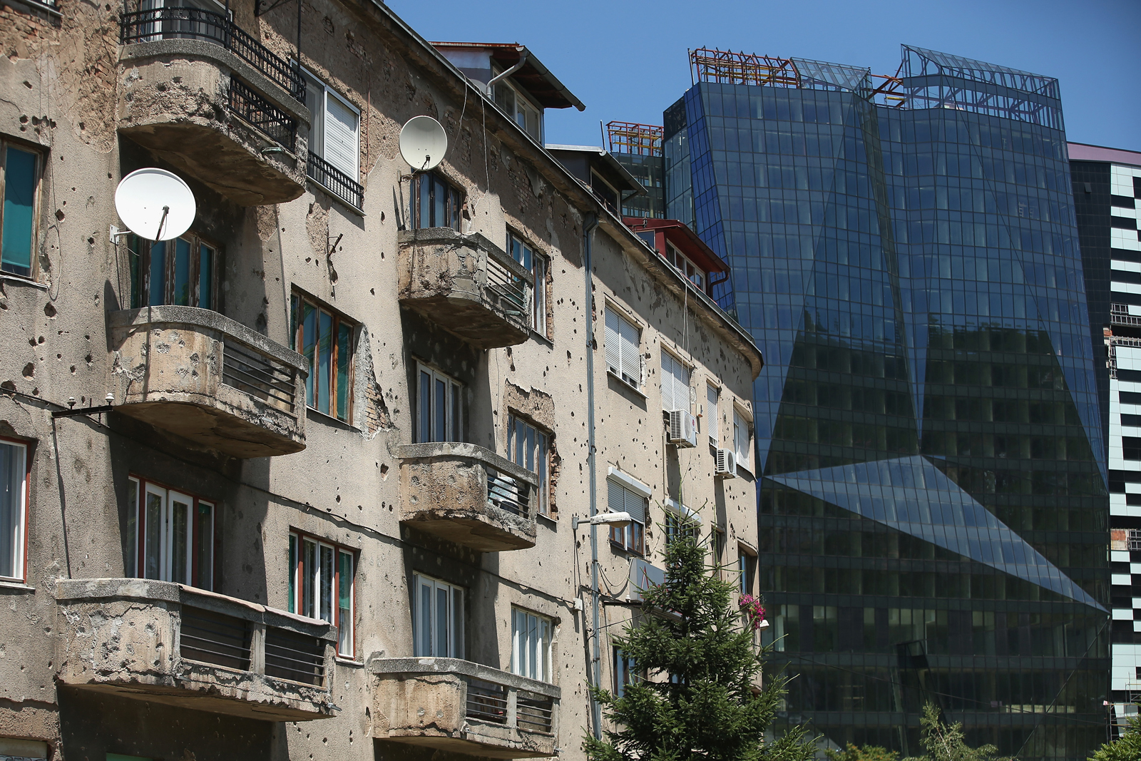 An apartment building with bullet holes from the 1992–1995 Bosnian War standing near a gleaming new office building, Sarajevo, Bosnia, June 29, 2014