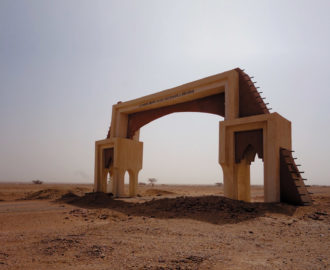 Agadez, Niger, 2018; the French inscription on the gate reads, 'The city of Agadez welcomes you'