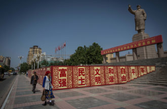 A Uighur woman walking past a statue of Mao Zedong in Kashgar City, northwestern Xinjiang, China, 2017