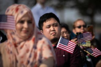 New American citizens hold American flags during a naturalization ceremony at Liberty State Park, Jersey City, New Jersey, October 2, 2018