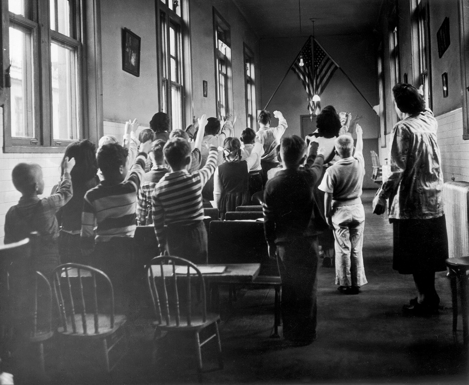 Children of immigrants pledging allegiance to the flag in a classroom on Ellis Island, 1940s
