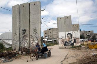Palestinians riding a donkey-drawn cart past a mural calling for a boycott of Israel, Khan Yunis, Gaza Strip, 2016