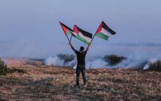 A Palestinian waving flags as tear gas disperses from canisters fired by Israeli troops during a protest near Khan Younis, Gaza Strip, March 22, 2019
