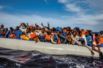 Refugees from Gambia, Mali, Senegal, Ivory Coast, Guinea, and Nigeria rescued by the Italian navy from a rubber boat in the sea between Italy and Libya, October 2014; photograph by Lynsey Addario from her book Of Love & War, published by Penguin