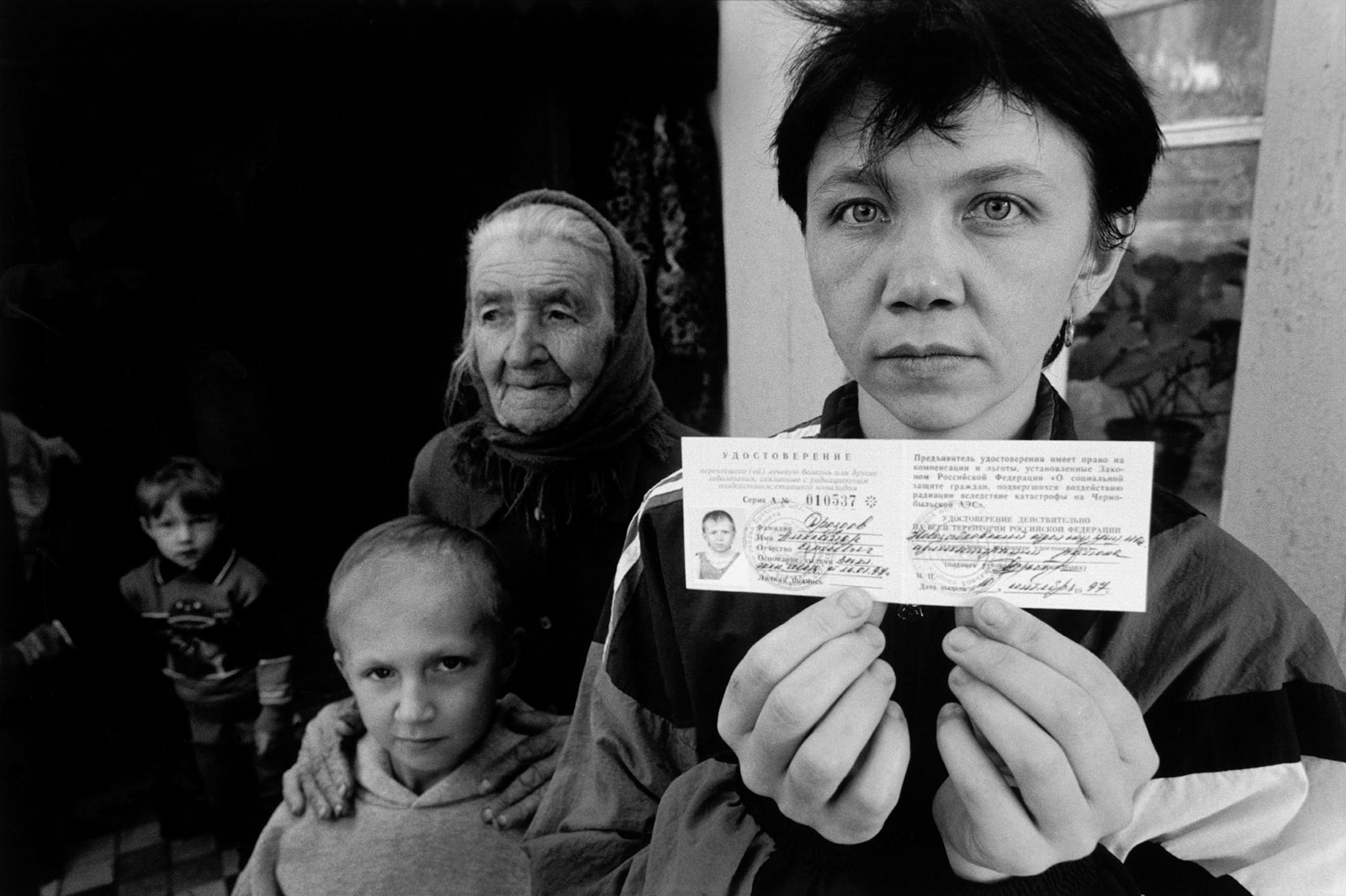 A mother holding a government document certifying that her daughter's brain tumor was caused by radiation from the Chernobyl disaster, Zamishevo, Russia, 1999
