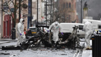 Forensic officers inspecting the remains of a van used as a car bomb in an attack by dissident Republicans outside Derry Court House, Northern Ireland, January 20, 2019