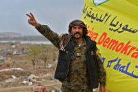 A member of the US-backed, Kurdish-led Syrian Democratic Forces flashing a victory sign next an SDF flag after the conquest of the Islamic State's final stronghold of Baghouz, in Deir al-Zour province, Eastern Syria, March 24, 2019