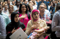 Mosammat Rasheda Akter (center), originally from Bangladesh, reciting the Pledge of Allegiance while holding her daughter after becoming a US citizen during a naturalization ceremony at the New York Public Library, July 2018