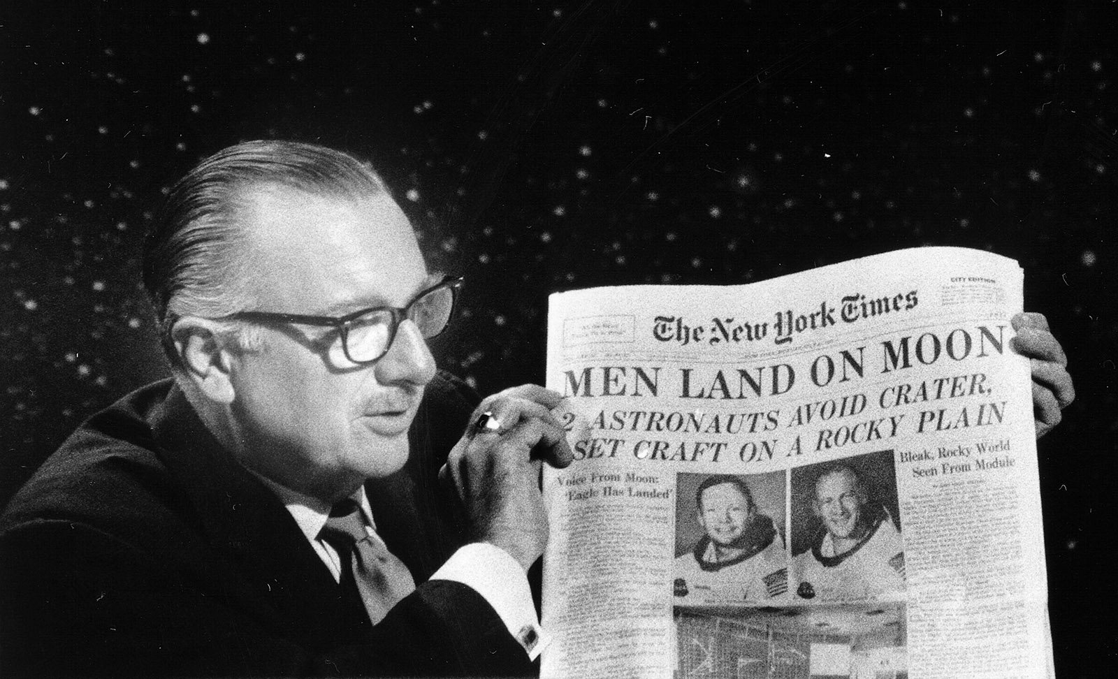 News anchor Walter Cronkite holds up an early edition of next day's The New York Times during CBS's Apollo 11 telecast, July 20, 1969
