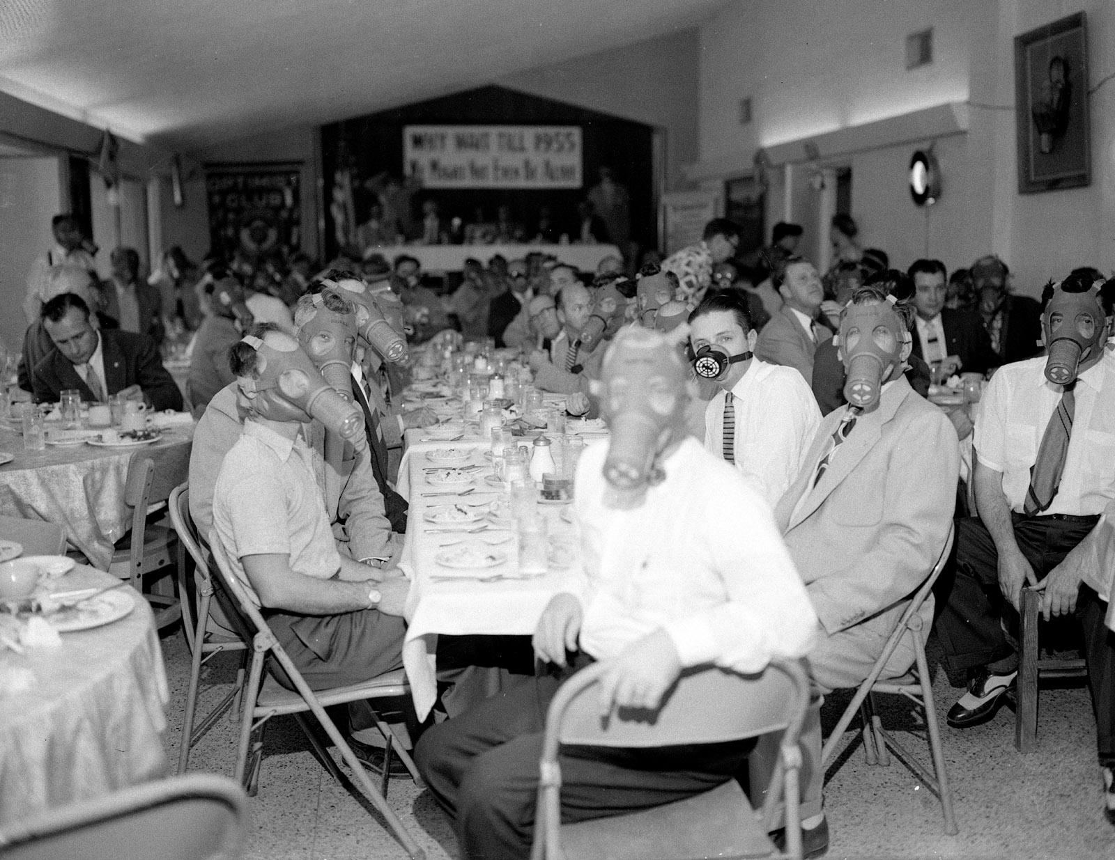 Highland Park Optimist Club members wearing smog gas masks at a banquet, Los Angeles, circa 1954