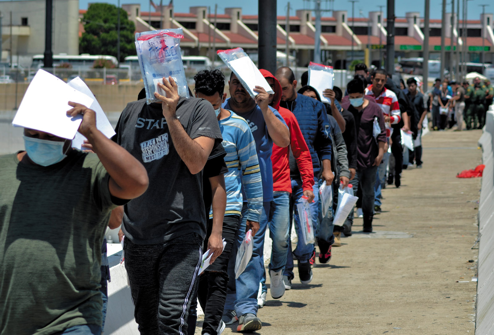 Migrants being returned to Mexico by United States Border Patrol officers under the Migration Protection Protocols, or Remain in Mexico program, Nuevo Laredo, Mexico, July 2019