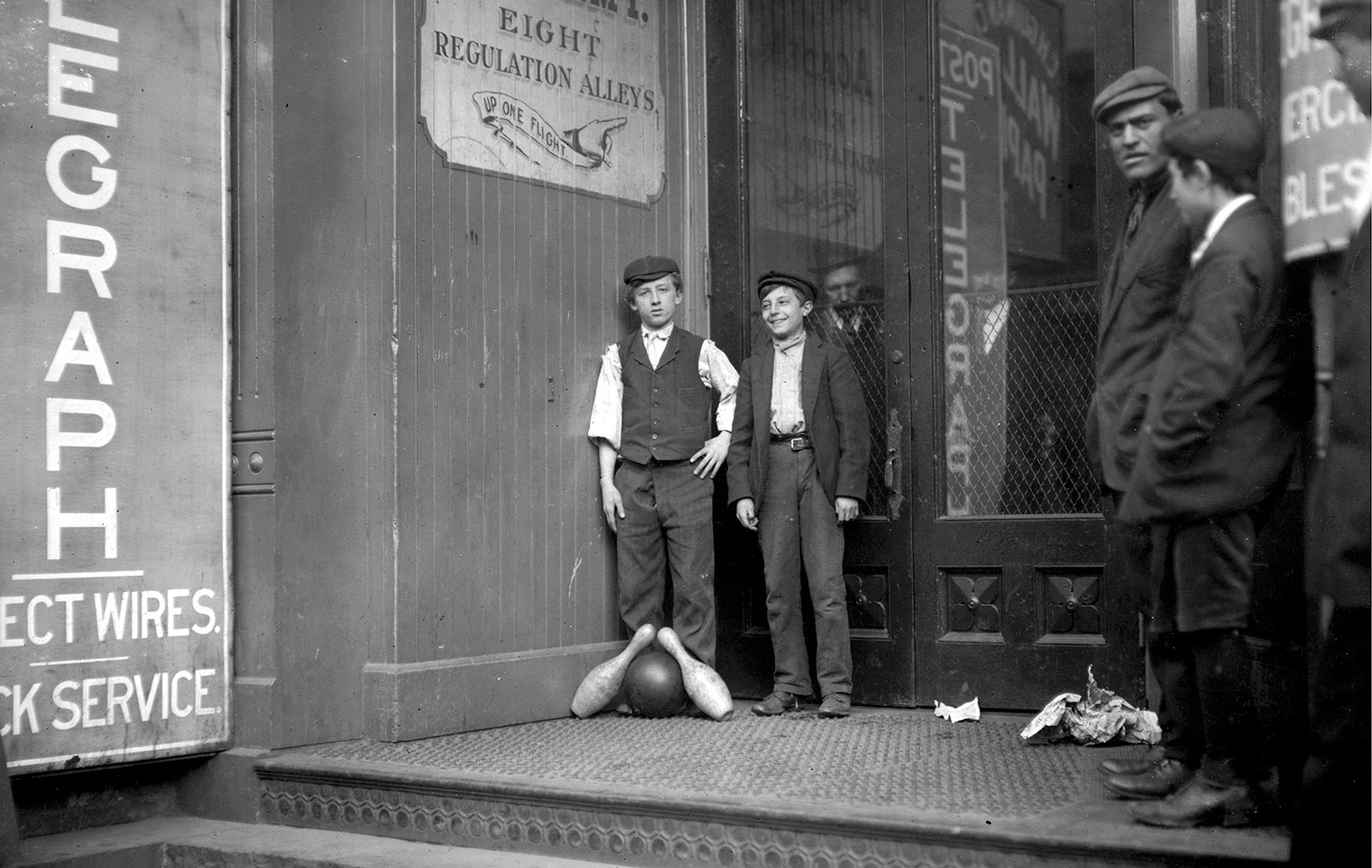 A pair of 'pinboys' posing for Lewis Hine with a bowling ball and pins, New Haven, Connecticut, 1909