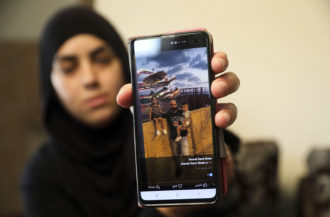 A relative showing a photo of Ahmed Manaa with his children at the family home after Manaa was killed, along with a brother, in a recent shootout in Majd al-Krum, northern Israel, October 7, 2019