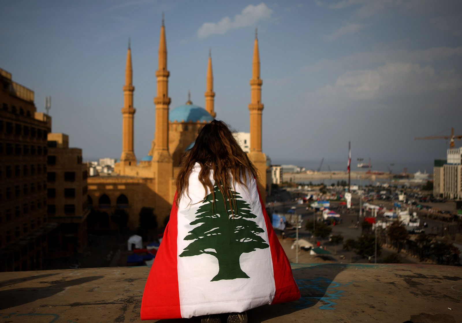 A Lebanese anti-government protester, draped in a national flag, sitting atop The Egg building overlooking the Mohammed al-Amin mosque and the Martyrs' Square, Beirut, Lebanon, November 14, 2019