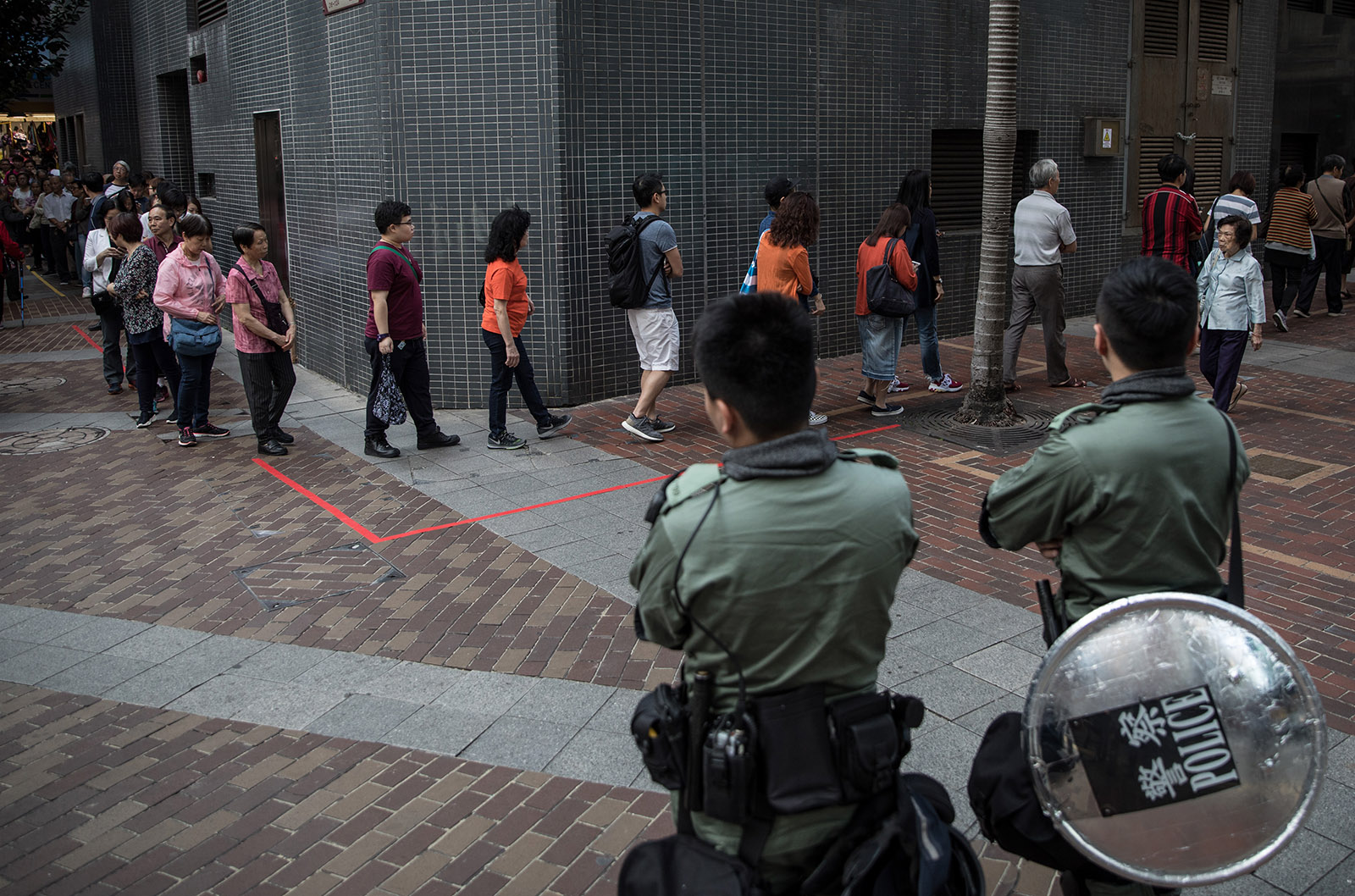 Police watching as people formed a line at a polling station to vote in district council elections, Hong Kong, November 24, 2019