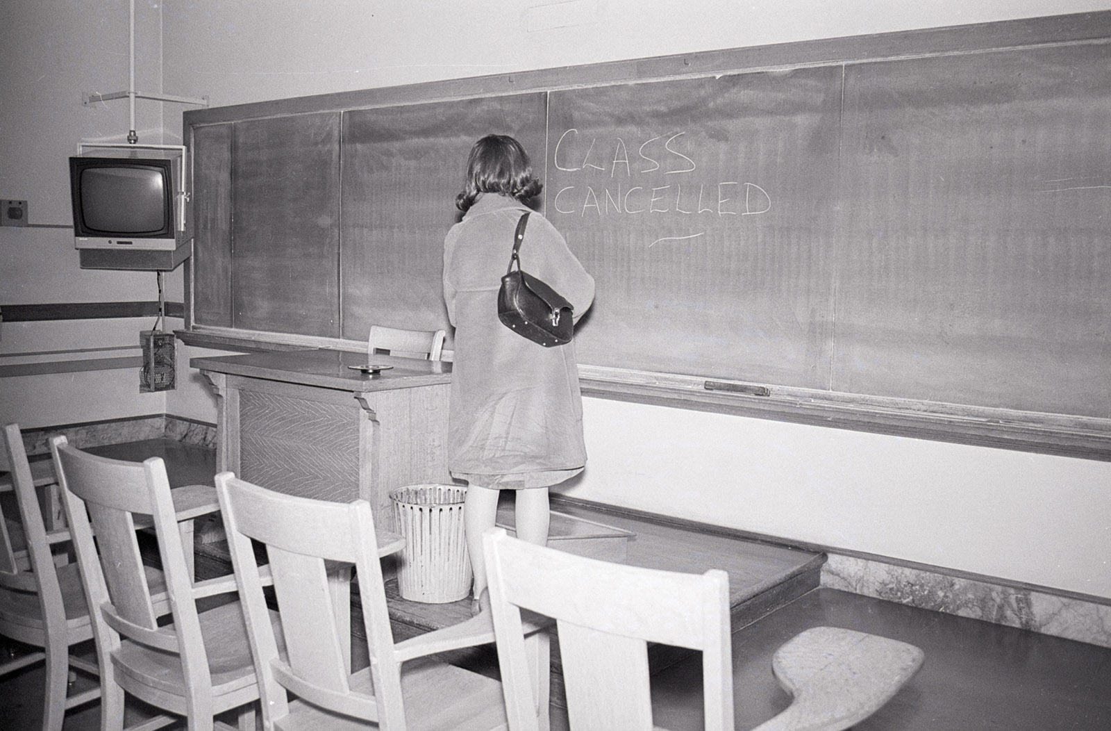 A University of California student stands in an empty classroom reading a notice of cancellation, Berkeley, 1964