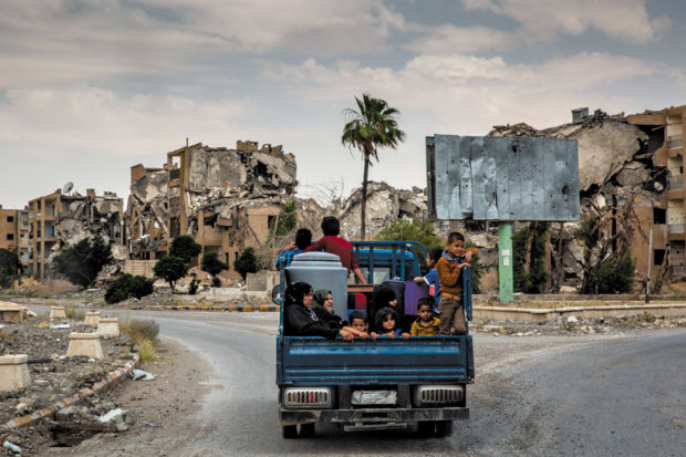 Family members returning to what remains of their neighborhood after years of being displaced by ISIS, Raqqa, Syria, June 2018; photograph by Ivor Prickett from his book <i>End of the Caliphate</i>, which includes an essay by Anthony Loyd and has just bee