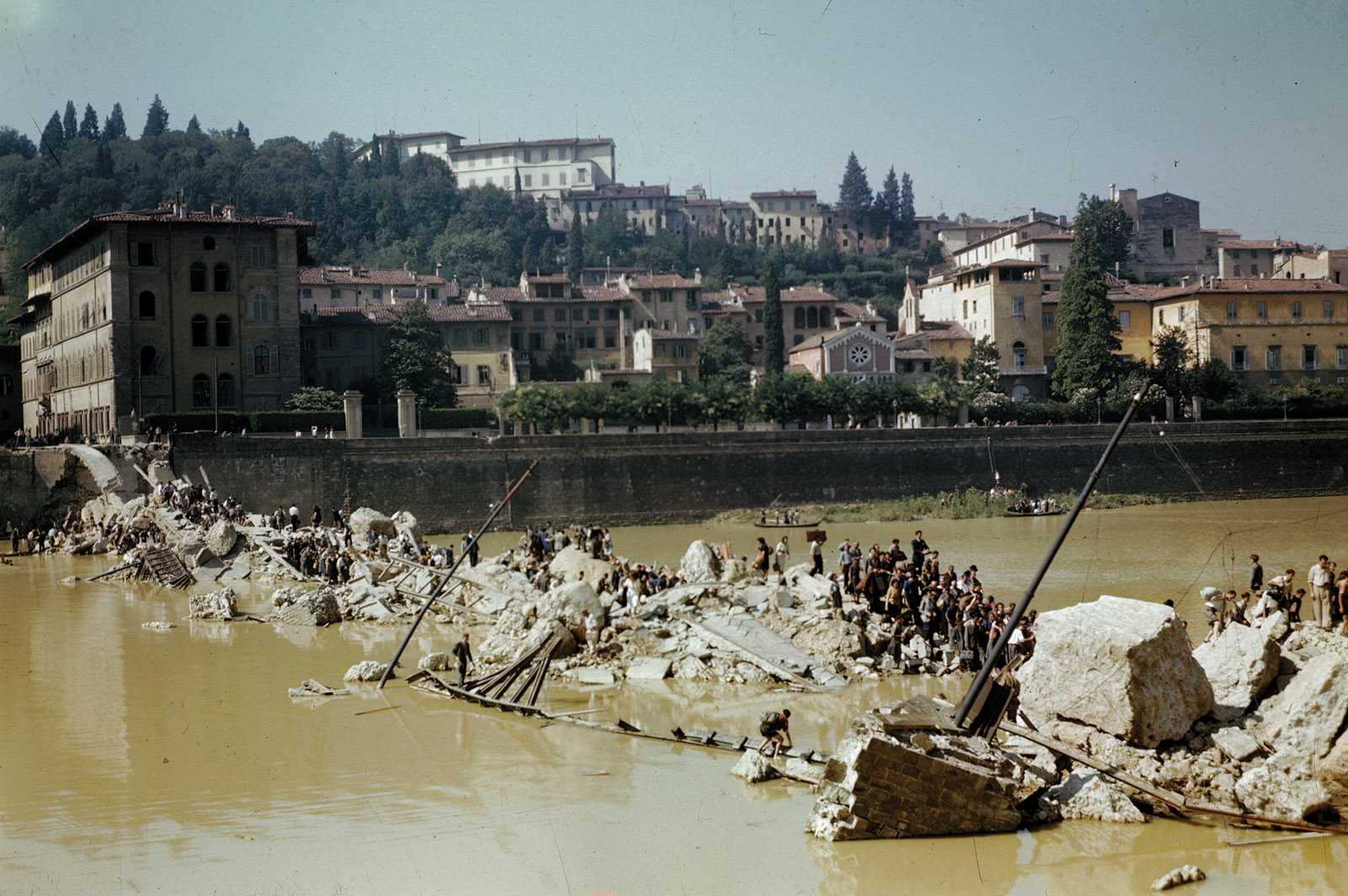 Italian civilians crossing the Arno River over the ruins of a bridge destroyed by German forces, Florence, April 1944